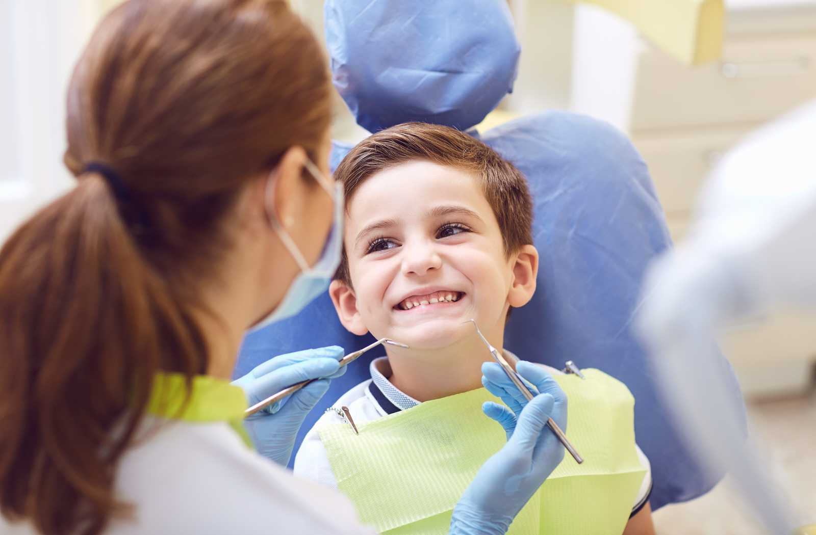 smiling child on blue chair learning to enjoy dental cleanings with woman holding scaling tools