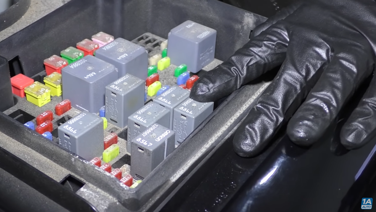 Mechanic pointing to a relay switch inside the fuse box.
