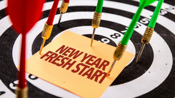 a dartboard laying flat with darts pinning down a paper reading new  year fresh start