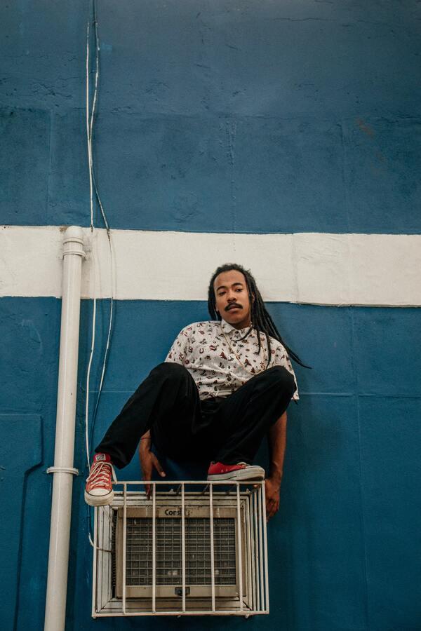 Homem negro em cima de uma grade com ar condicionado