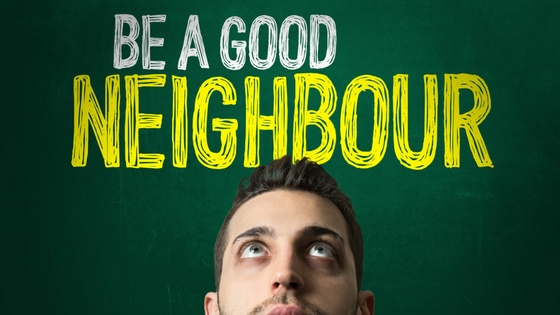 The picture shows the top half of a man's face (like he's looking over a fence) underneath the words Be a Good Neighbor in white and yellow lettering on a green background.