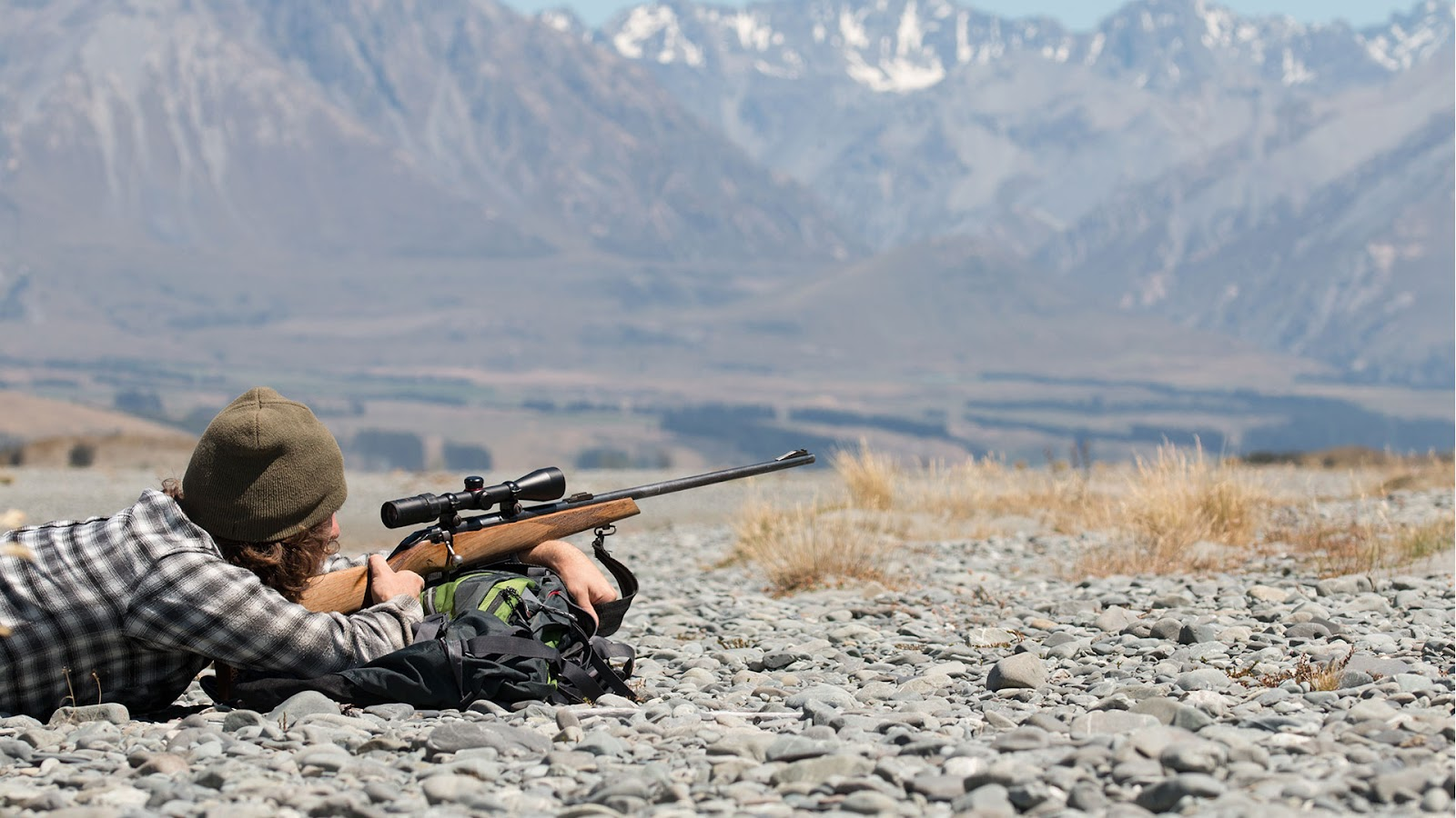 Hunter with rifle in the mountains
