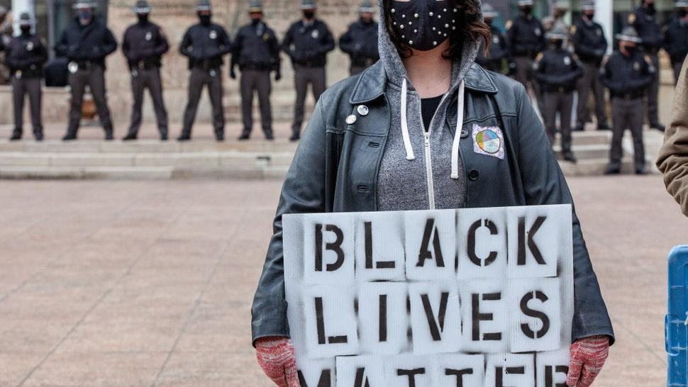 Woman holds a Black Lives Matter sign in front of a line of Ohio State Troopers in from of the Ohio Statehouse.