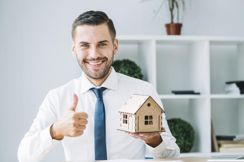 courtier immobilier de montréal en chemise blanche souriant à la caméra avec le pouce levé et une maison cartonnée dans l'autre main
