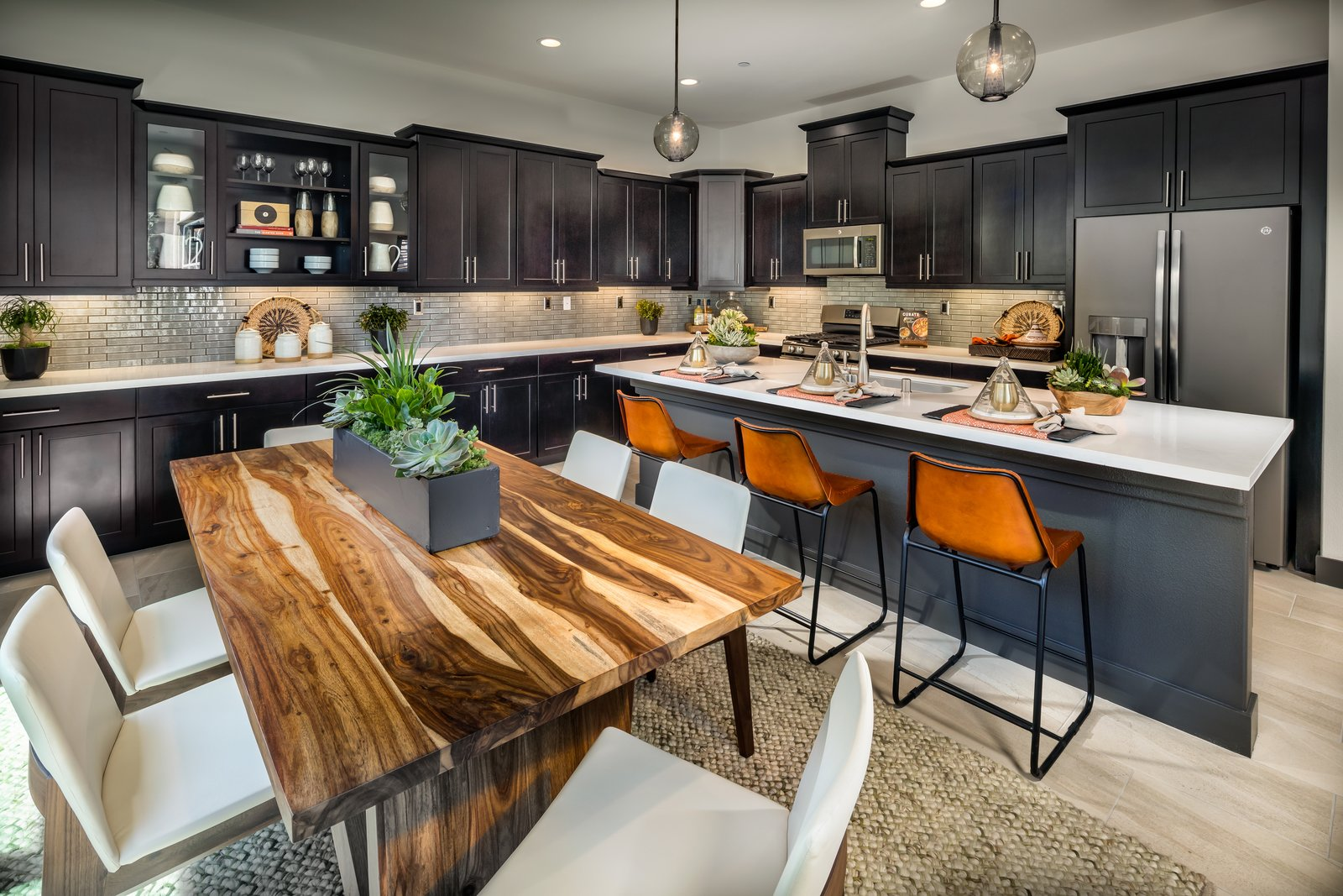 large kitchen with natural wood dining table, island with leather barstools, dark espresso shaker cabinets, stainless steel appliances and led cabinet lighting