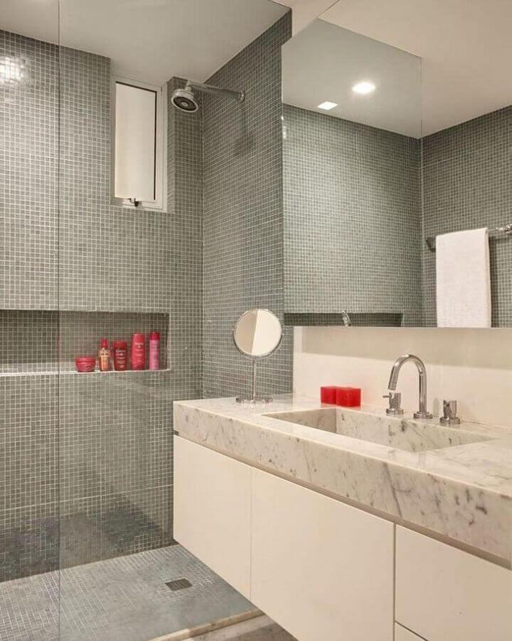 Banheiro revestido de pastilhas cinzas, box de vidro, gabinete branco e pia marmorizado.