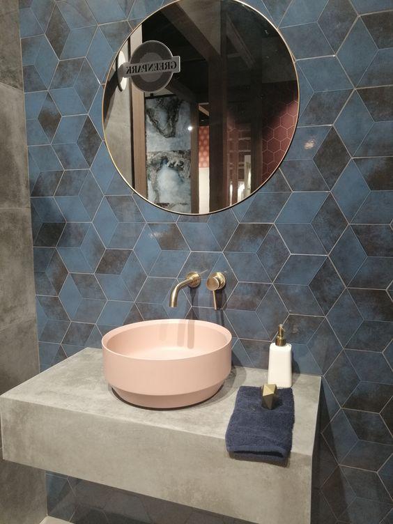 banheiro com revestimento hexagonal com estampa de mosaico azul e preto na parede, bancada da pia de cimento queimado com cuba rosa e espelho redondo.