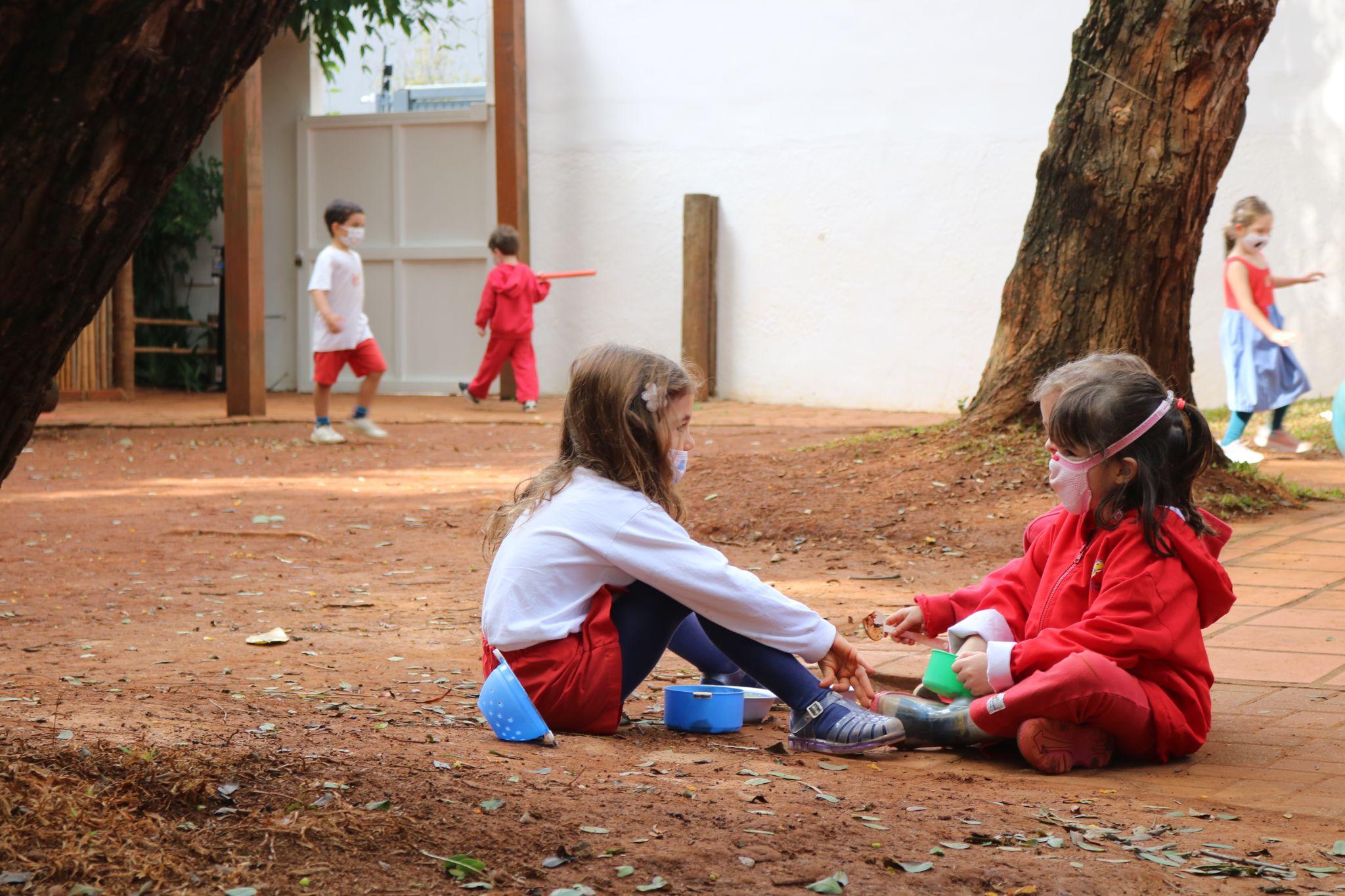 A imagem mostra crianças conversando sentadas em um quintal de terra.