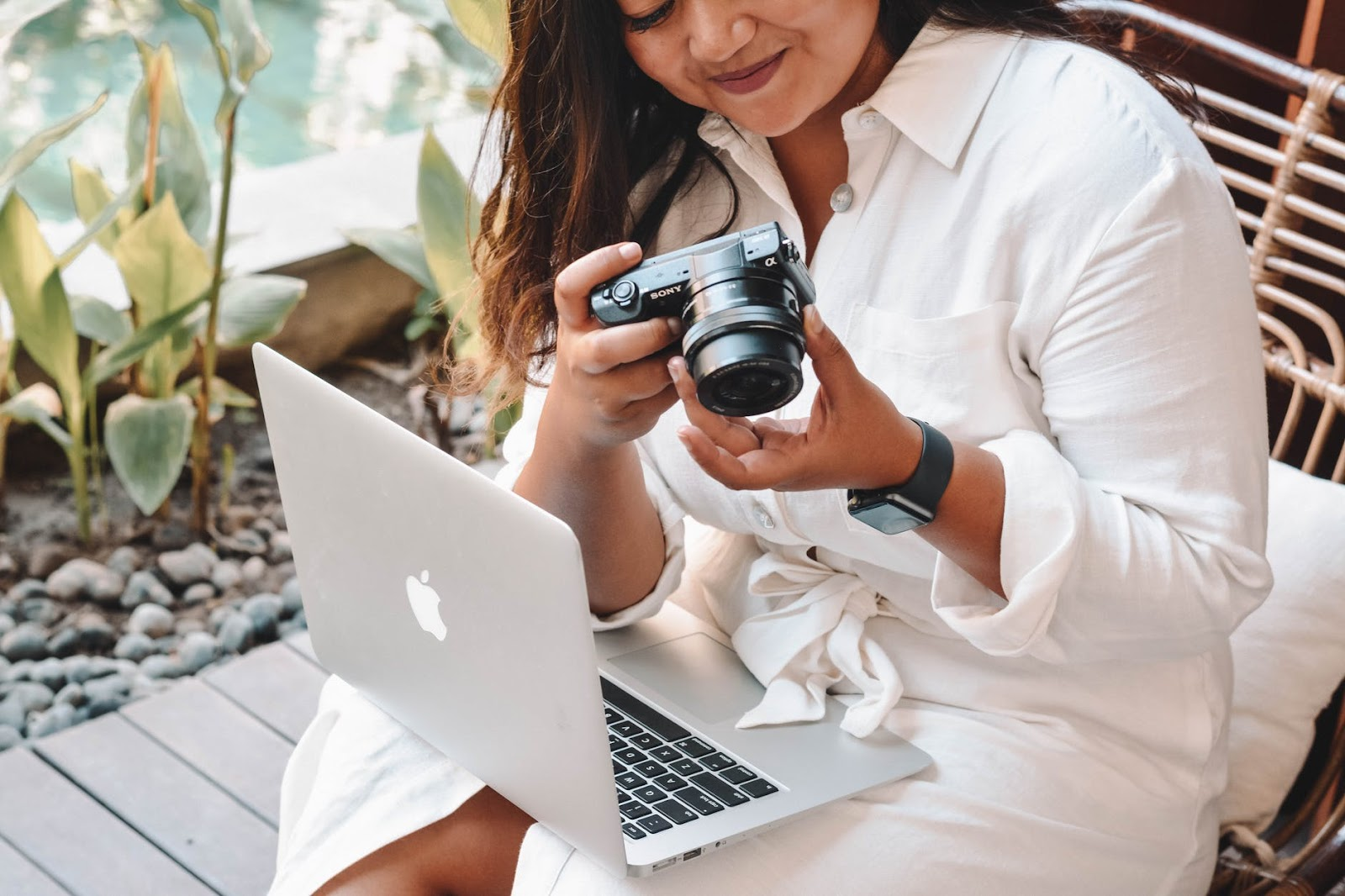 woman holding camera with laptop