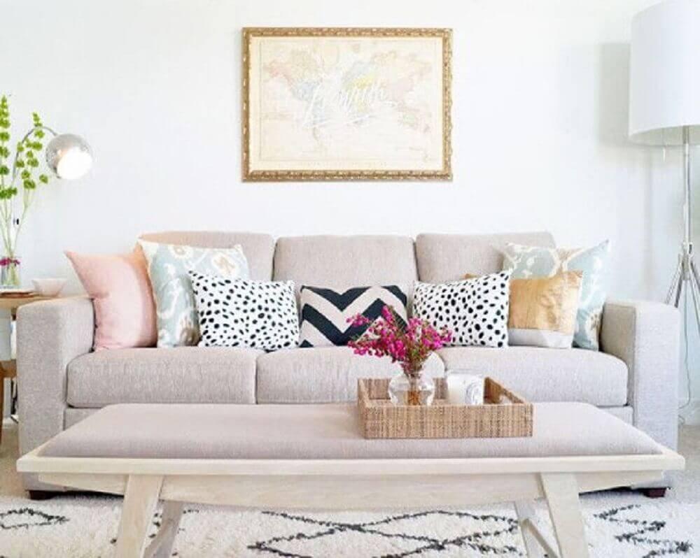Vista frontal de um sofá de 3 lugares cinzas, com 7 almofadas coloridas, em sua frente temos uma mesa de centro com um vaso e, na parede, logo acima e centralizada ao sofá, um quadro. Imagem para ilustrar a reforma de casas.