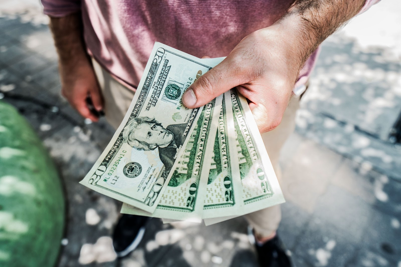 man handing over 20 dollar bills