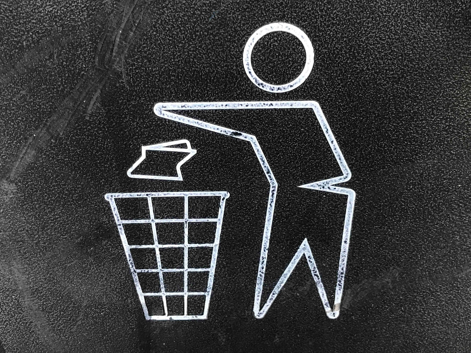 Drawing of a person sketch putting paper in a trash can