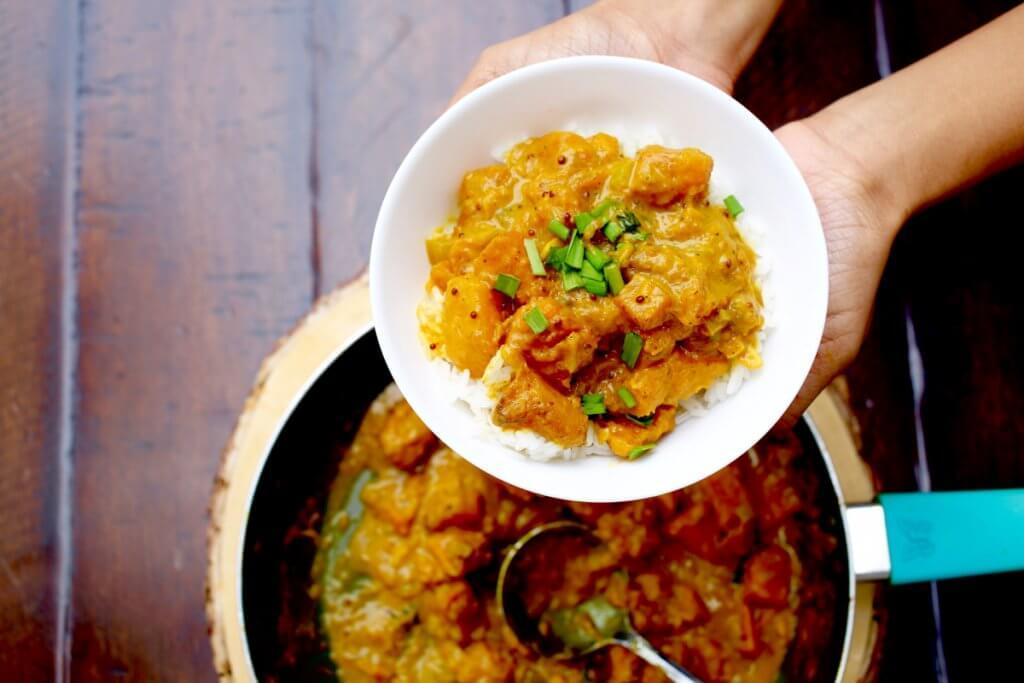 Top View of hands holding bowl of South Indian Squash Curry with Rice