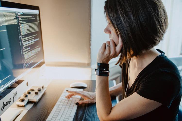 Mulher sentada de frente para o computador programando - Mulheres na programação