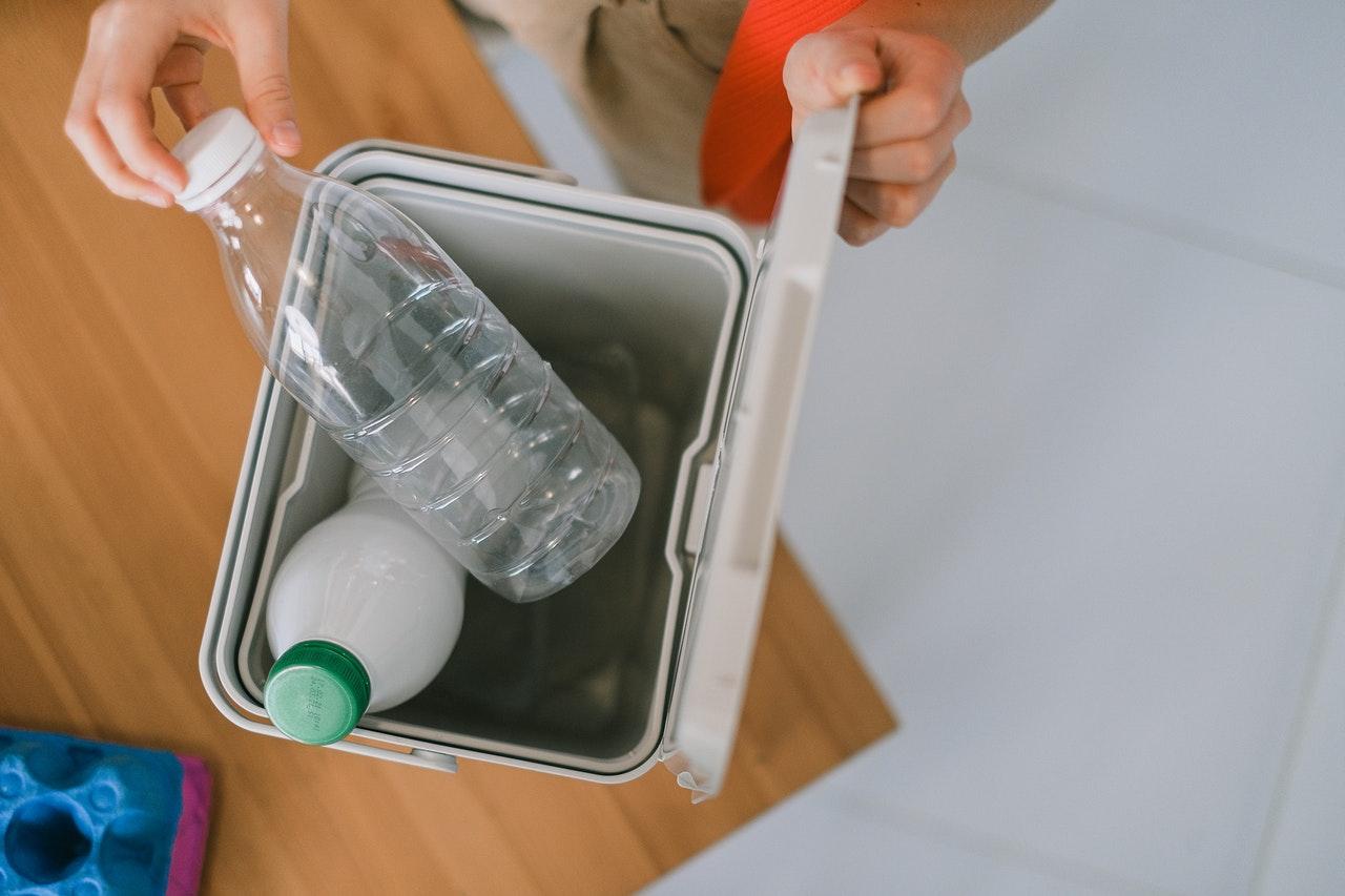 Pessoa separando plásticos para a reciclagem