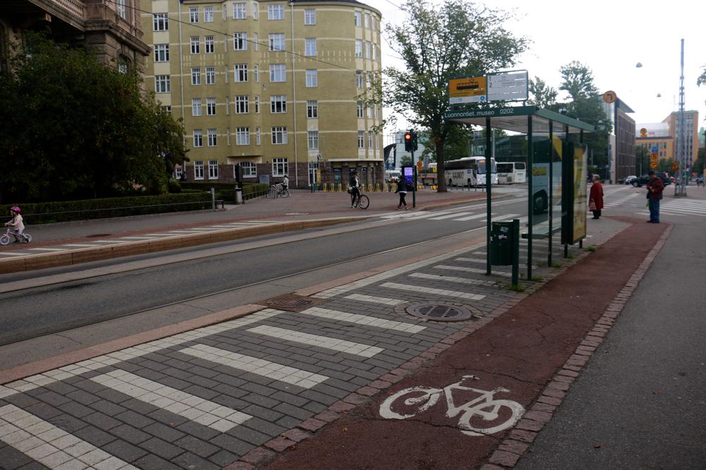 Rua com ciclofaixa, ponto de ônibus e pedestres