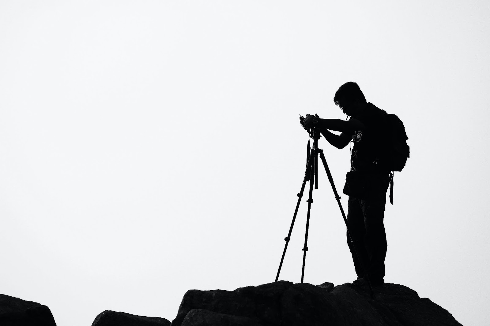 This picture is used in an article about camera gear rental insurance. A photographer is pictured filming on-top of a mountain.