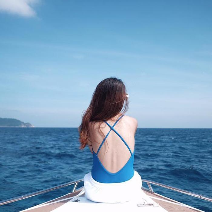 Blue crossback one piece swimsuit against the turquoise ocean and blue sky.