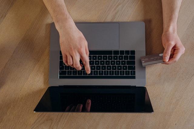 Imagem vista do alto. Mão digitando em notebook enquanto a outra segura um cartão de crédito.