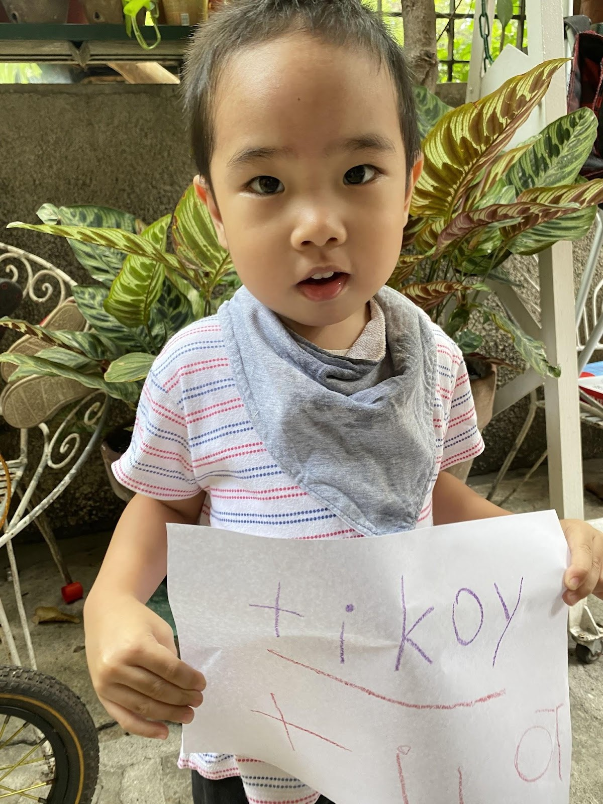 Toddler practices writing his name.