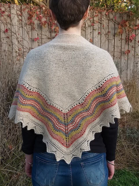 Siobhan stands against a garden fence. She wears a triangular handknit shawl across her shoulders; in beige with red, orange, yellow and grey/blue coloured lace stripes.