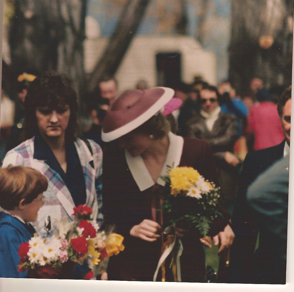 Princess Diana gathering flowers from a child, captured on a polaroid camera.