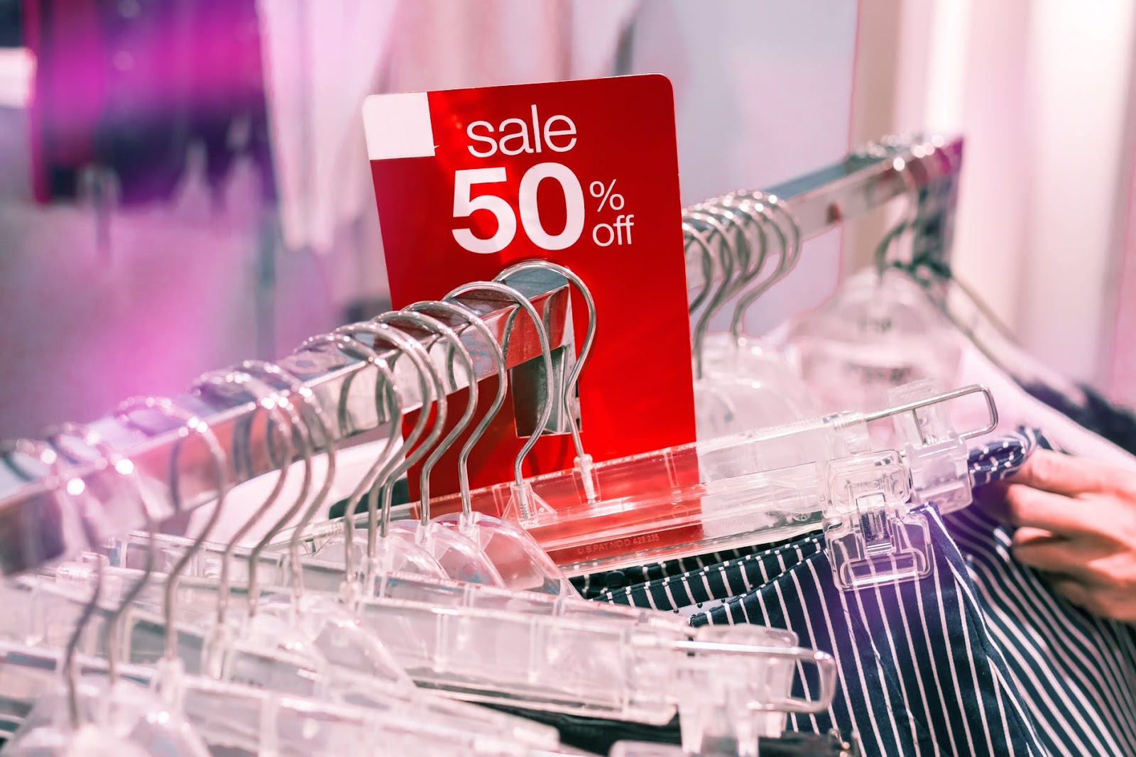 "Apparel in hangers with ""sale 50% off"" placard."