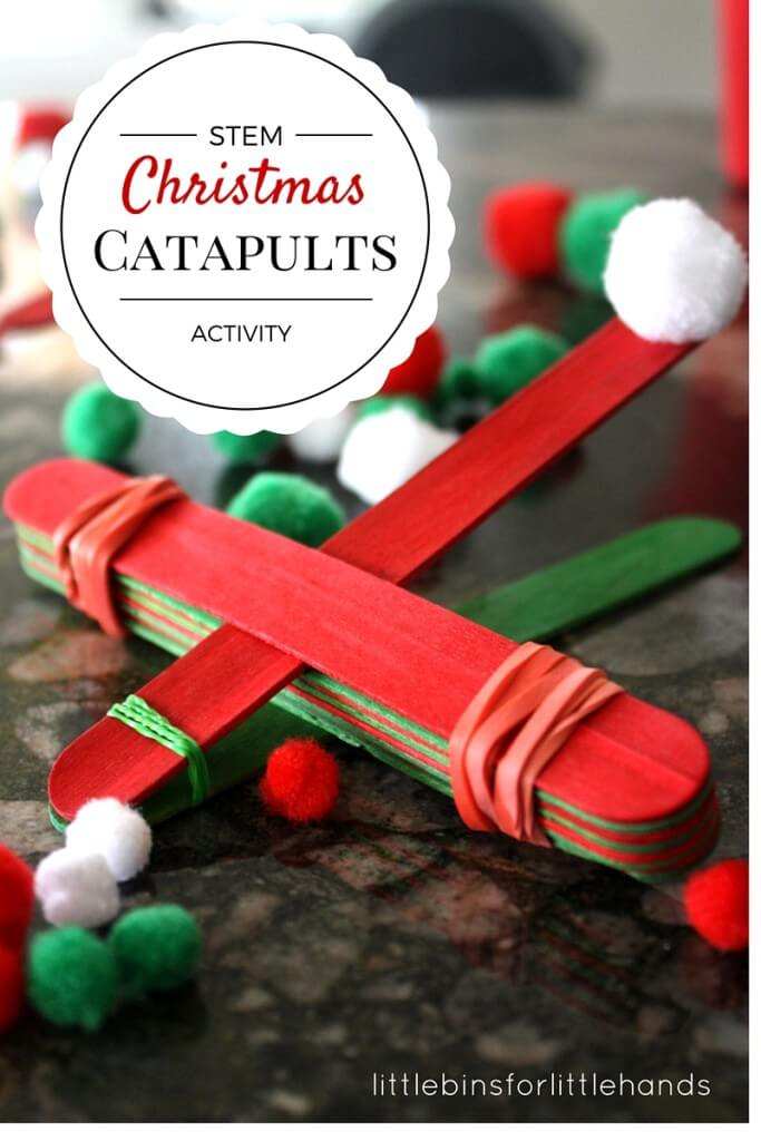 A catapult made out of red and green popsicle sticks and rubber bands prepares to shoot a white cotton ball.