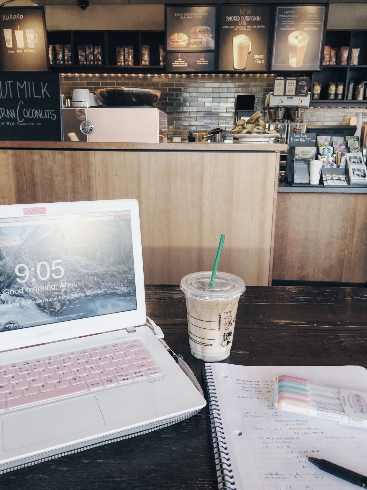 A laptop and coffee on a table in a Starbucks