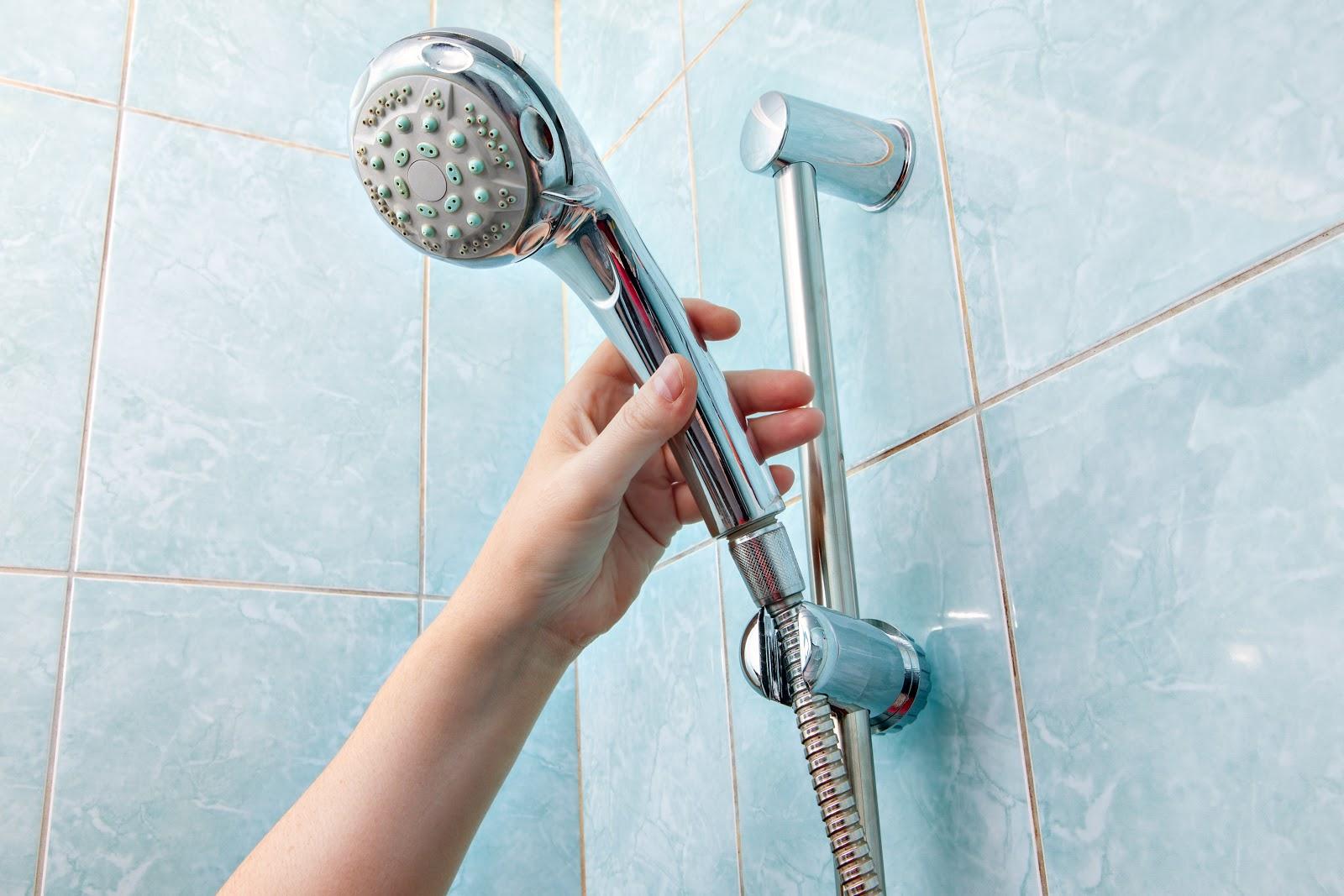 Uma mão segurando em um chuveiro.