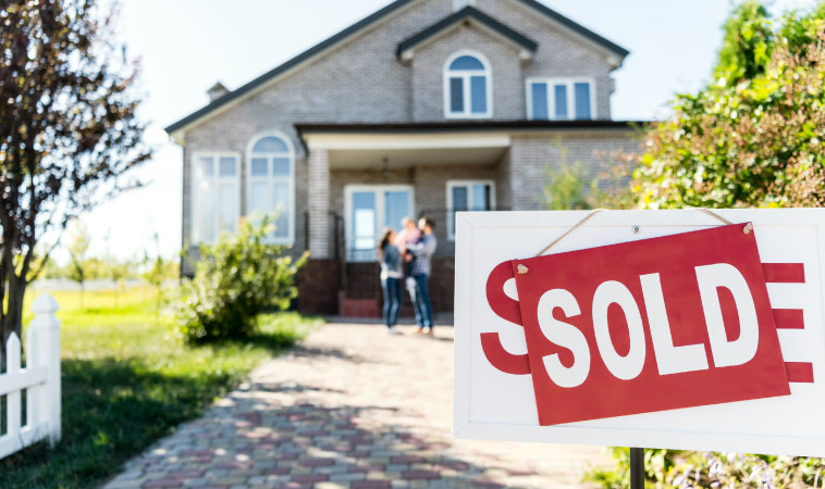 A family standing in front of their new home with a sold sign in front