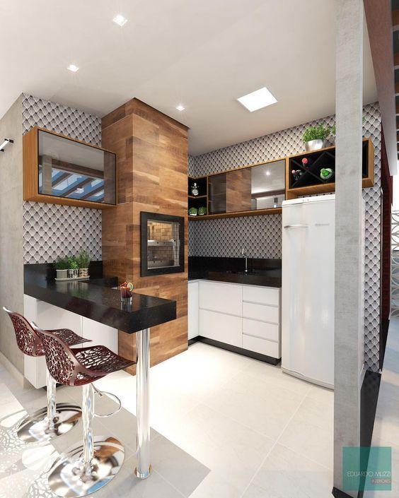 Area gourmet com churrasqueira revestida de porcelanato amadeirado, pia e bancada revestida de granito preto, armários brancos e amadeirado e piso porcelanato branco.