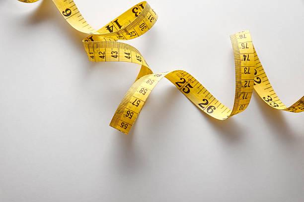 Yellow tape measure in meters and inches in a spiral