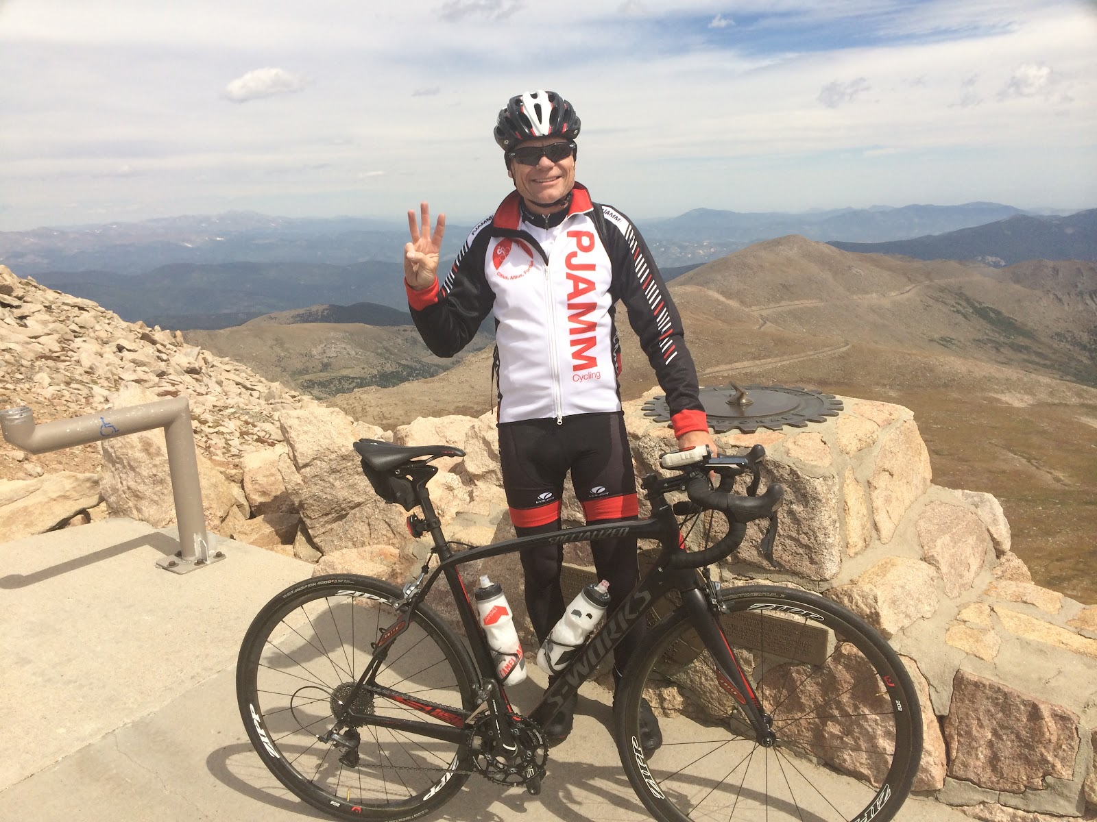 PJAMM cyclist at summit of Mount Evans with bicycle