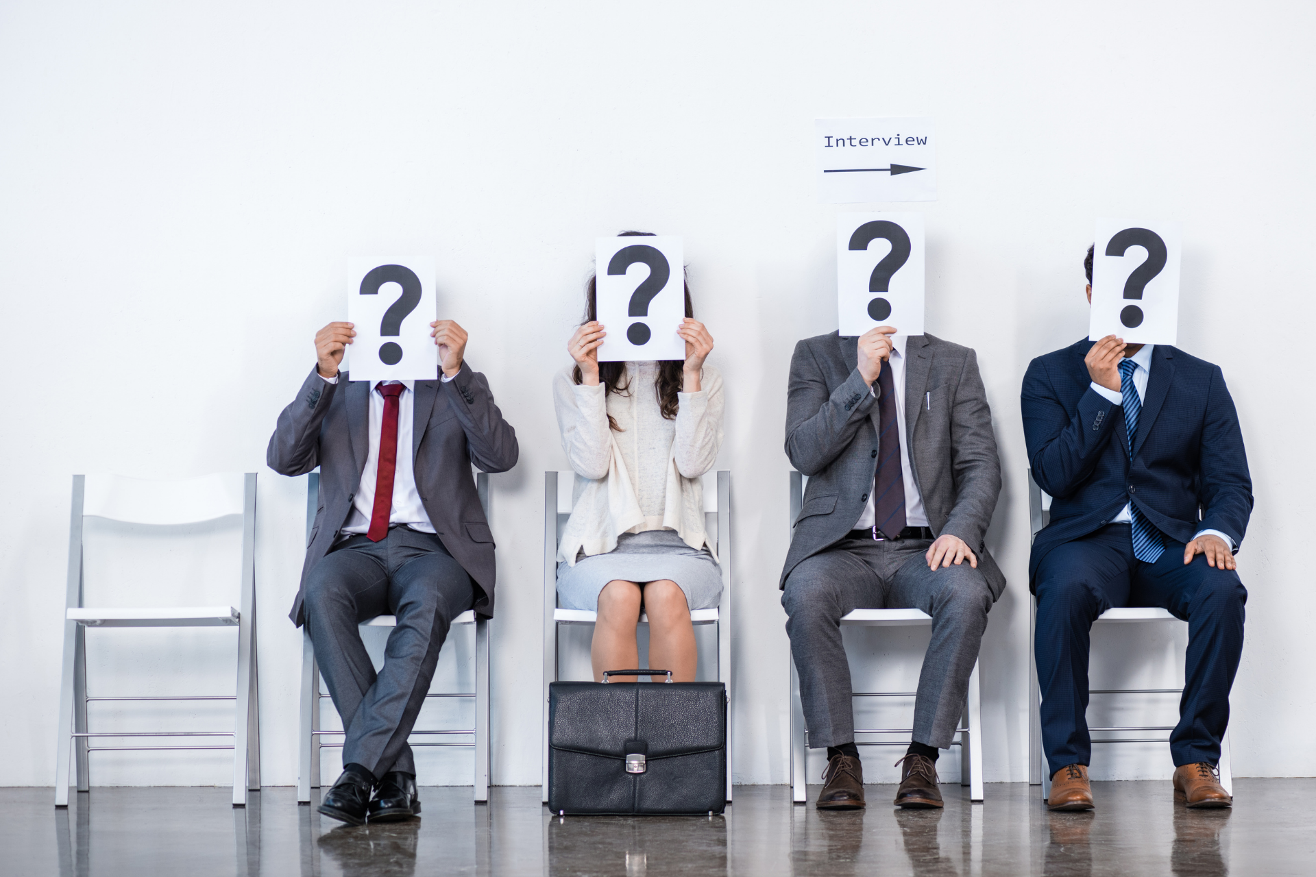 A lineup of potential employees with question marks covering their faces