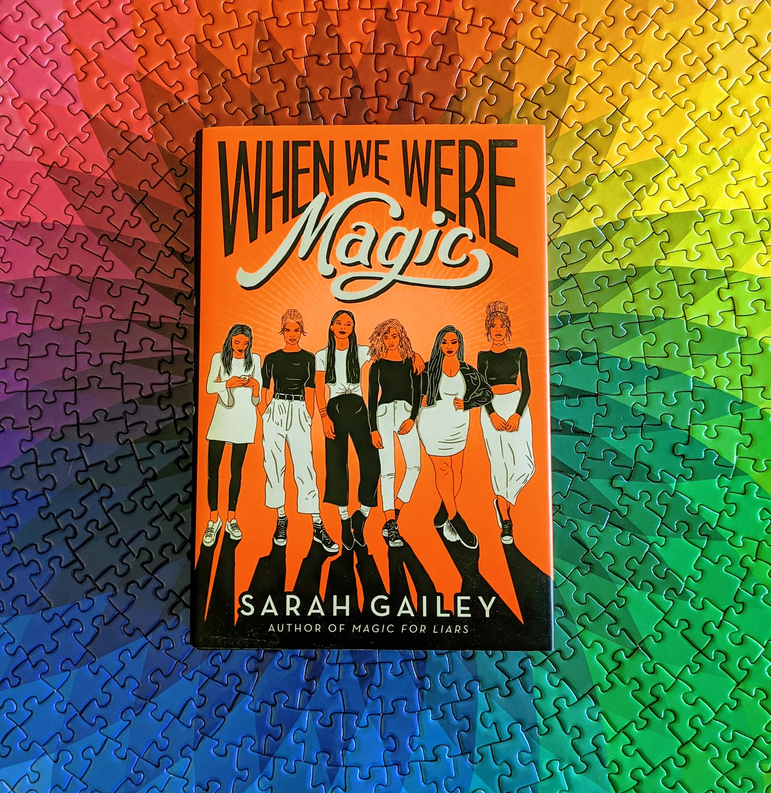 When We Were Magic, a neon orange book featuring six teen femmes in black and white clothing, resting on top of a puzzle that is a rainbow spirograph.