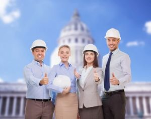 Group of construction workers, wearing formal clothing with helmets