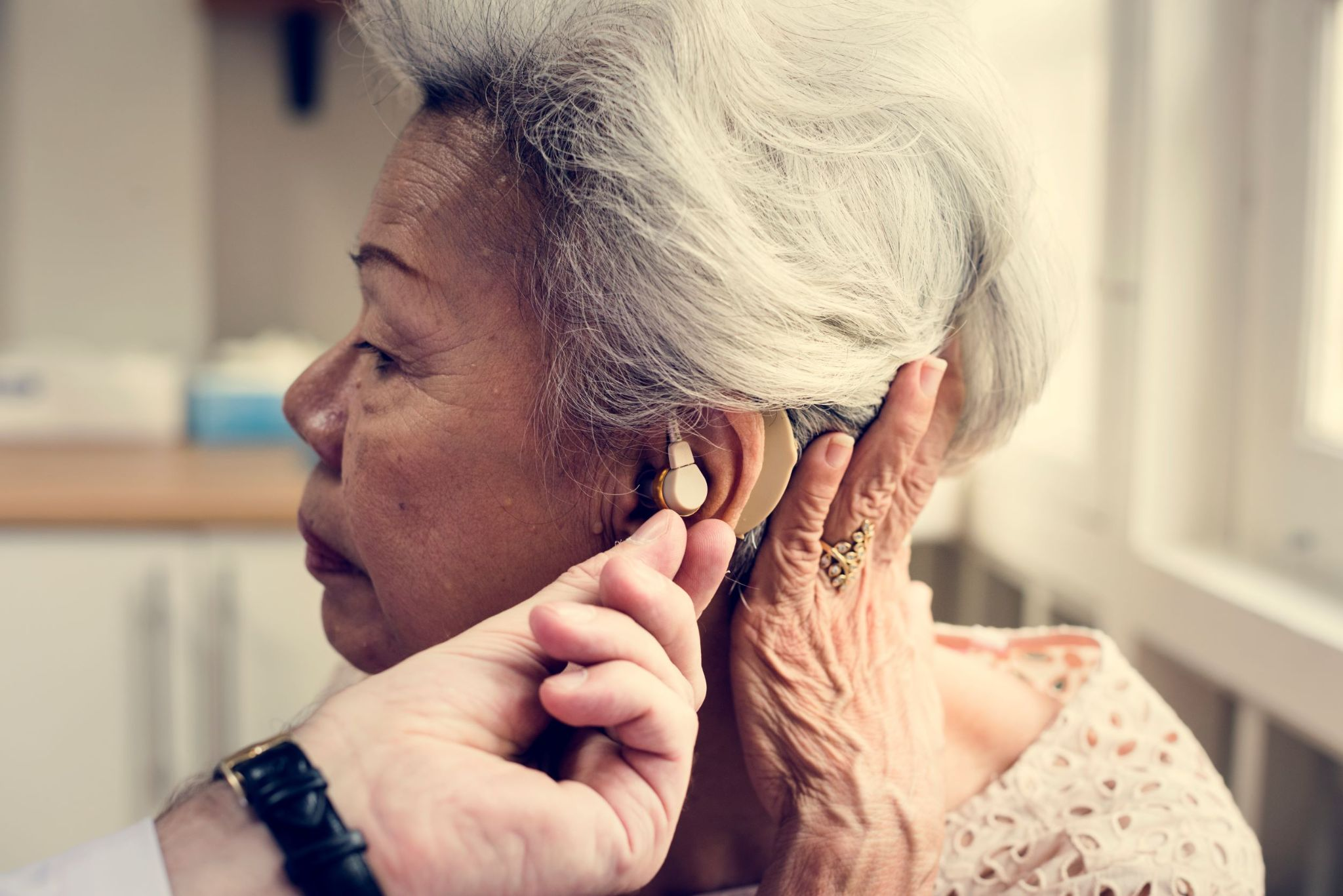 older-woman-getting-hearing-aid-adjusted