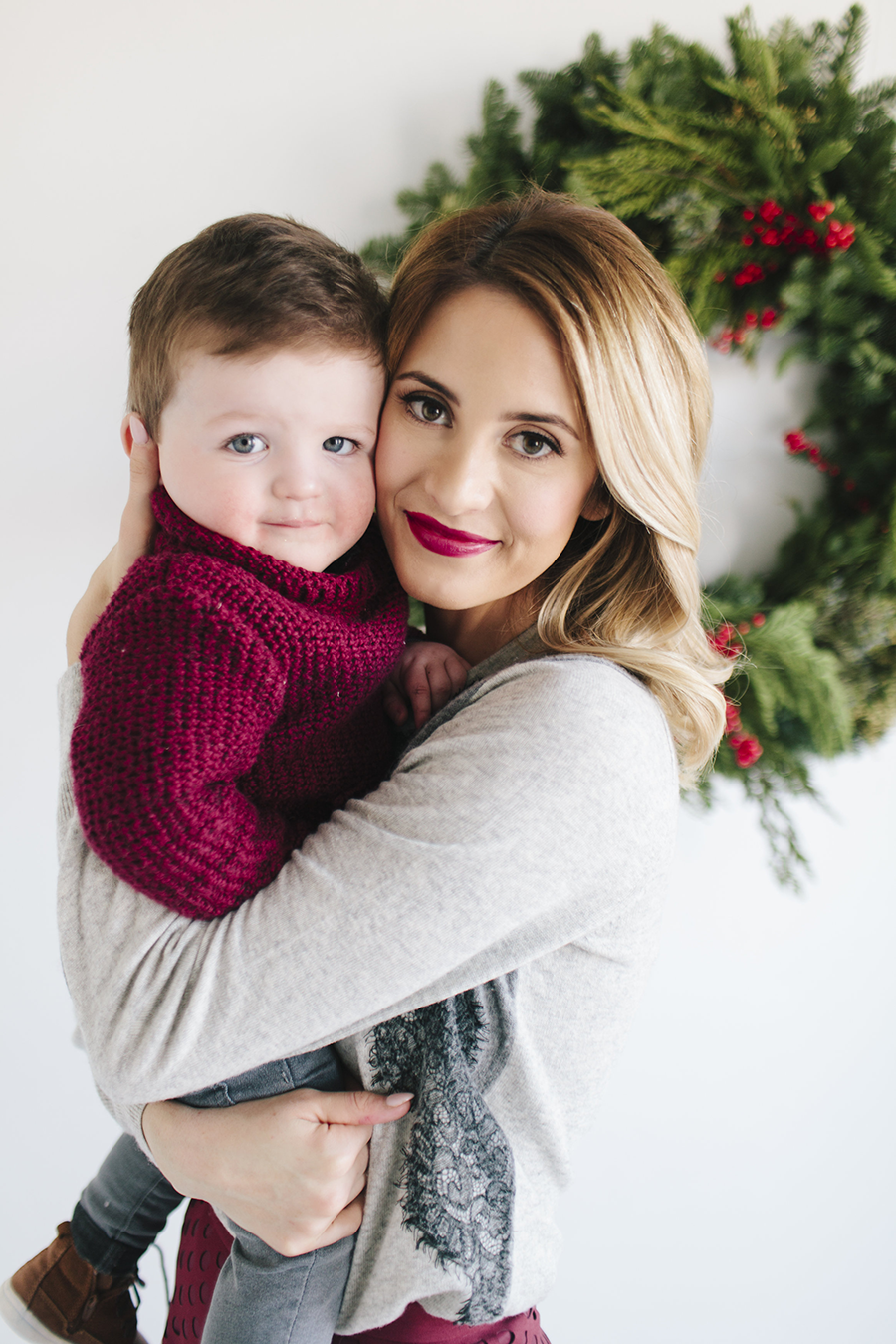 fun christmas card pose of mom and son in front of a wreath with chrismas sweater