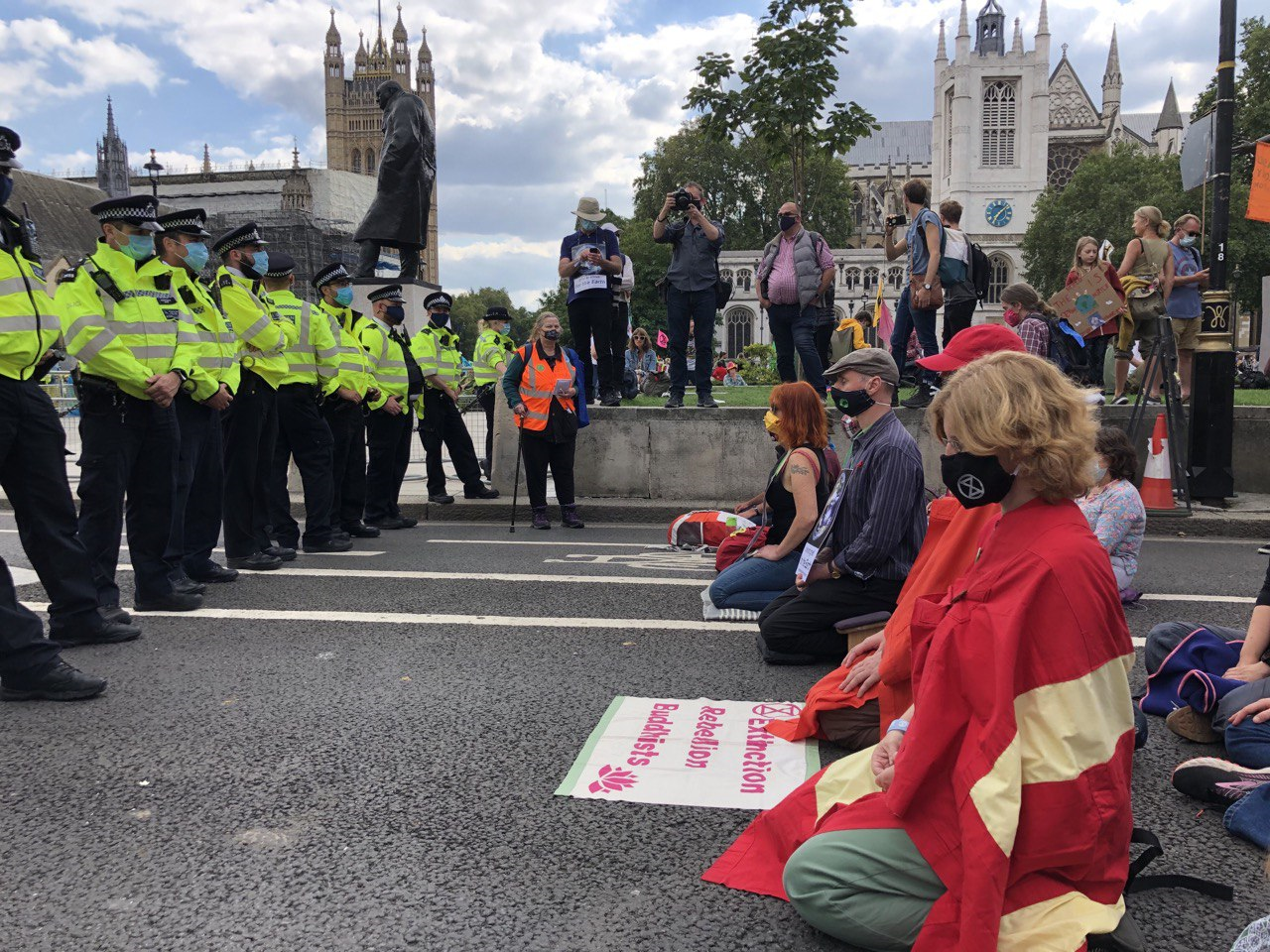 Members of XR Buddhists sitting in the road in Parliament Square in front of lines of police.