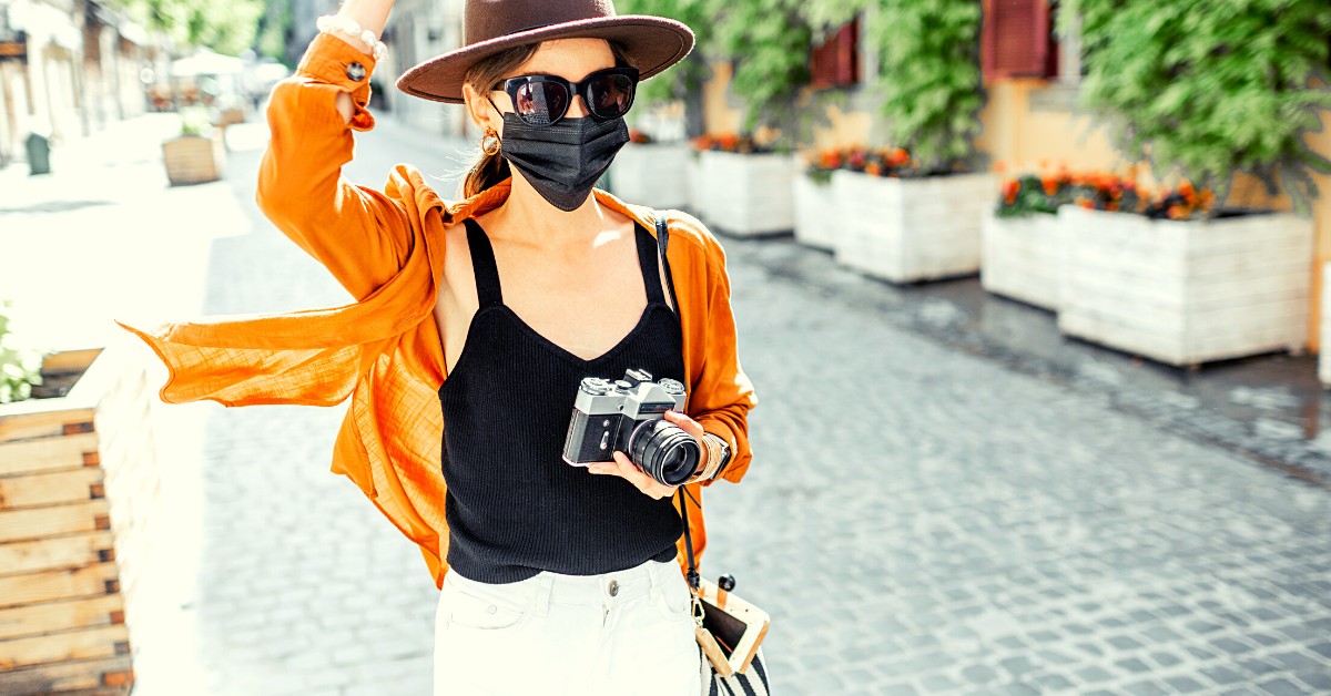 A woman wearing a mask, traveling and holding a camera in her hand.