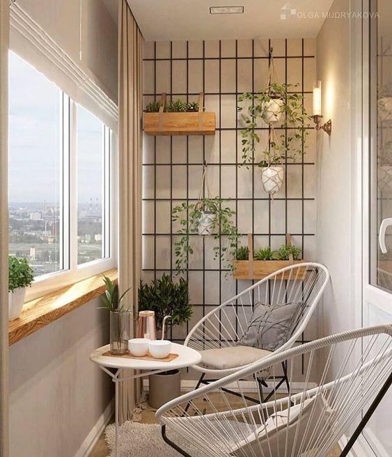 Varanda com jardim vertical, cadeiras de ferro e mesinha branca de centro.