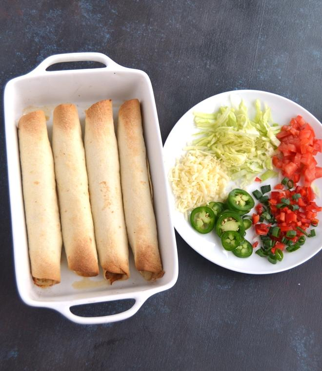 Baked Chicken Taquitos are filled with shredded chipotle chicken and melted cheese and are perfectly crispy. Topped with tomatoes, jalapeno, lettuce, sour cream, cheese and green onion for a delciious appetizer or meal! www.nutritionistreviews.com
