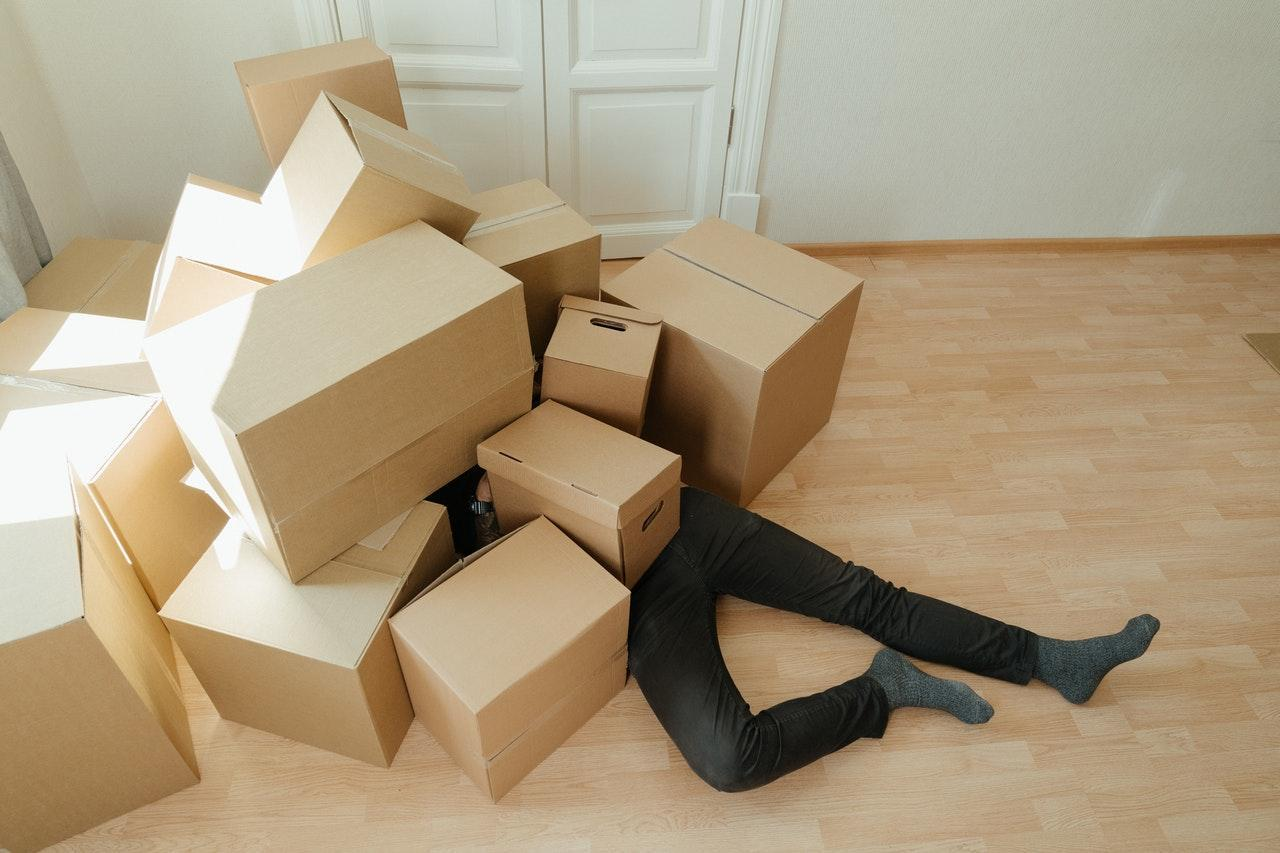 Alt-tag: A man laying on the floor with a pile of boxes on his upper-half.