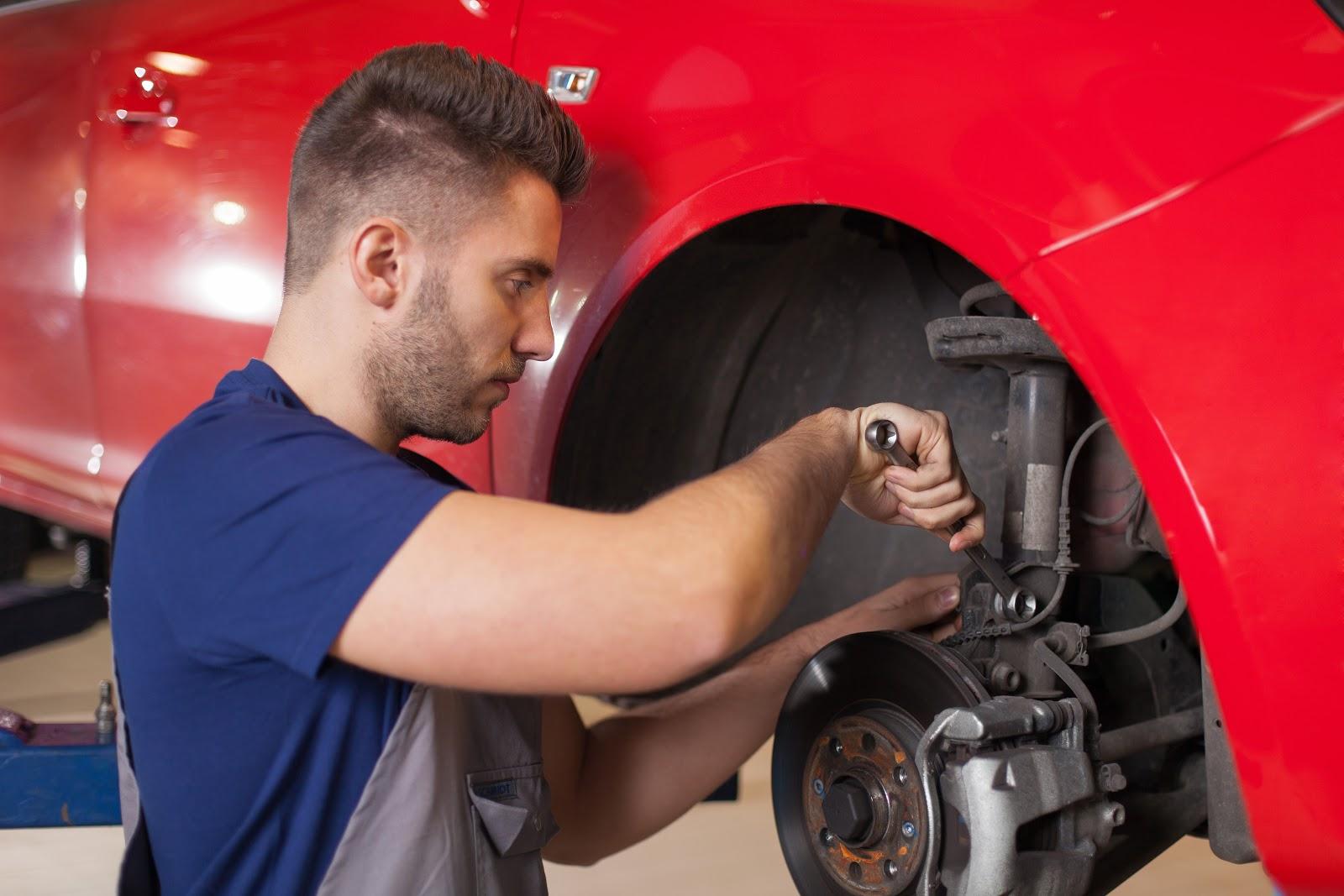 Um mecânico concentrado em consertar um carro.