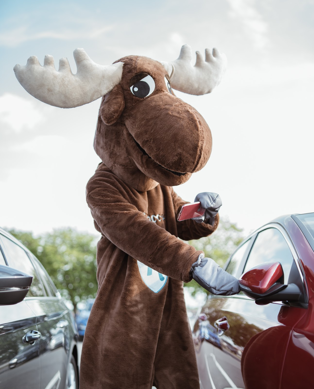 Rental Moose mascot is photographing the condition of the red Kia rental car. It is crucial to document the damage on a rental car before driving away.
