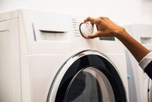 Person Adjusting Control on Front-load Clothes Washer
