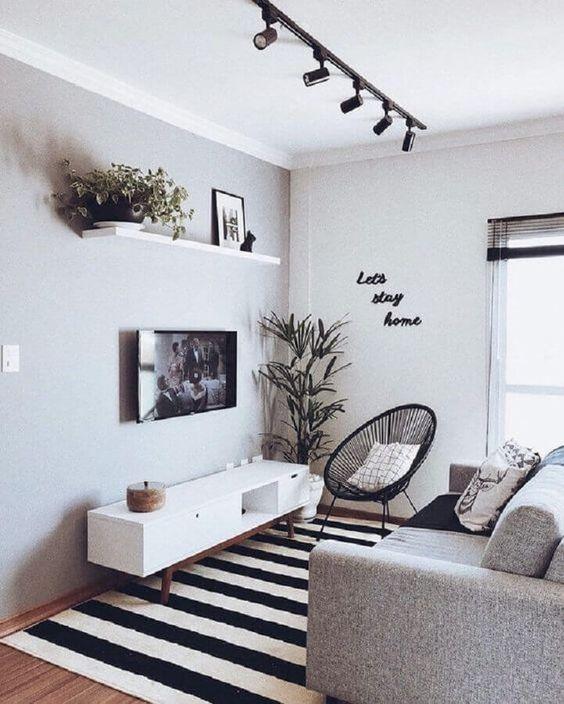 Sala moderna com vasos de planta na decoração, poltrona preta, sofá cinza, rack branca e tapete listrado.