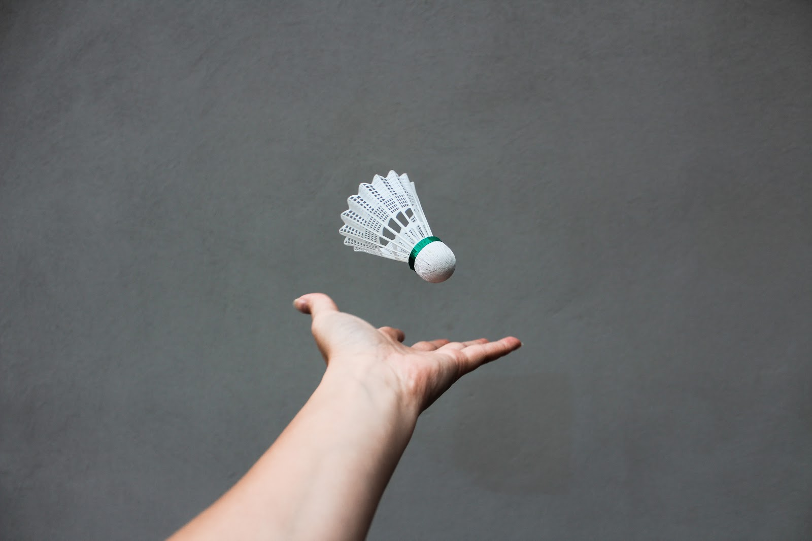 This is an image of a hand tossing a white synthetic shuttlecock up into the air.