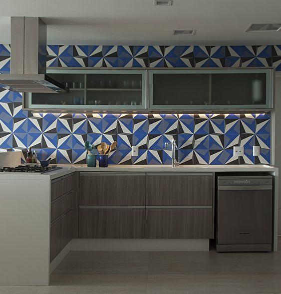 Cozinha com revestimento geométricos nas cores azul, cinza, preto e branco, armários e piso cinza.